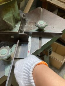 ダンボールの角を切る機械で寸法を測っているところ