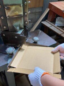 ダンボールの角を切る機械で四隅を切る